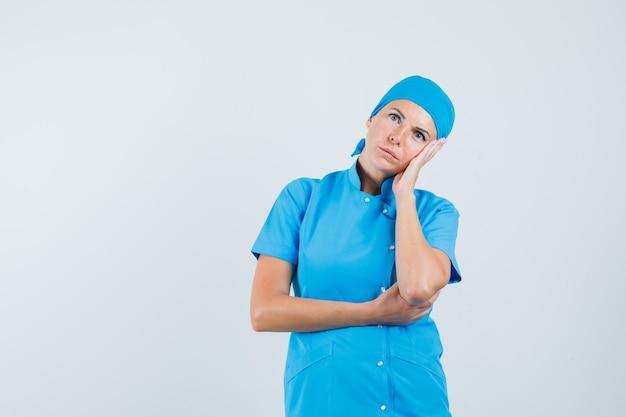 Médica encostando a bochecha na palma da mão em uniforme azul e parecendo pensativa. vista frontal.