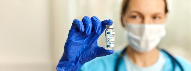 Médica, enfermeira, cientista com estetoscópio, usando luvas azuis segurando coronavírus, doença da vacina covid-19 se preparando para a vacinação, conceito de bandeira de medicamento.