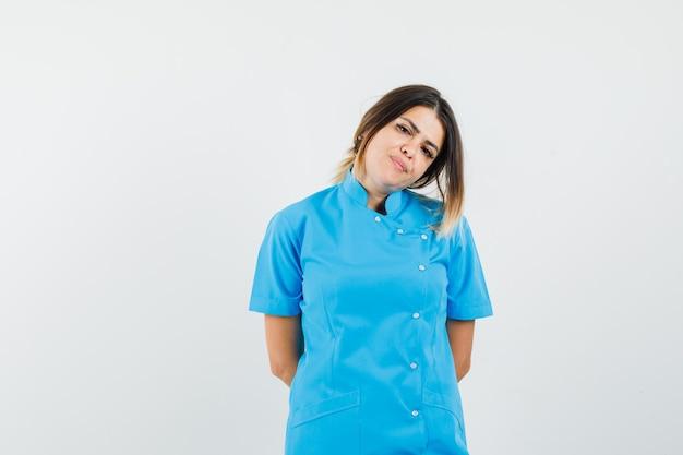 Médica escondendo as mãos nas costas com uniforme azul e linda