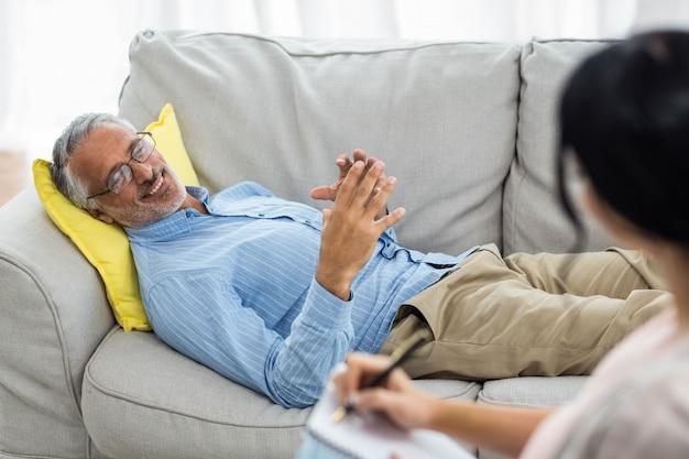 Médica, escrevendo no bloco de notas ao consultar um homem em casa