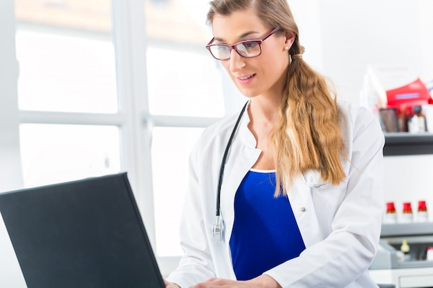 Médica, escrevendo no pc em sua clínica