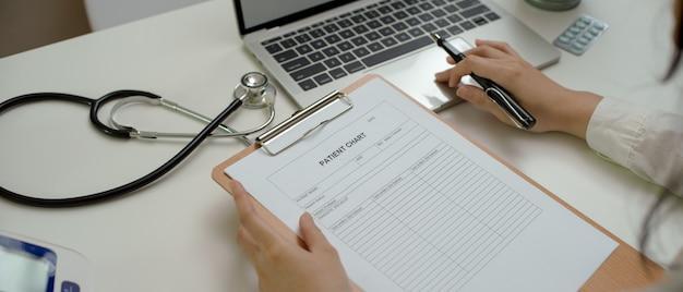 Médica, escrevendo o atestado médico no laptop enquanto procura informações na ficha do paciente