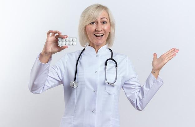 Médica eslava adulta surpreendida com túnica médica com estetoscópio segurando o comprimido do medicamento em embalagem blister e mantendo a mão aberta, isolada no fundo branco com espaço de cópia