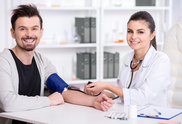 Médica está verificando a pressão arterial do paciente.