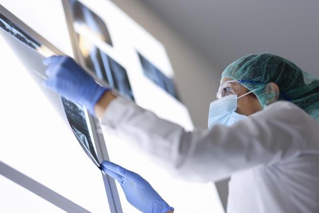 Médica examina radiografia de paciente na sala de cirurgia