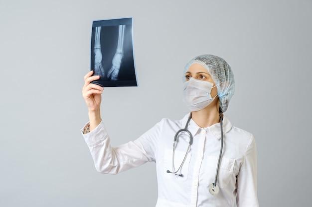 Médica examinando a imagem de raio-x das pernas de um bebê recém-nascido. isolado sobre parede cinza