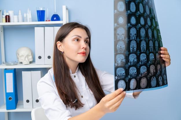 Médica examinando a imagem de rm do paciente em seu escritório