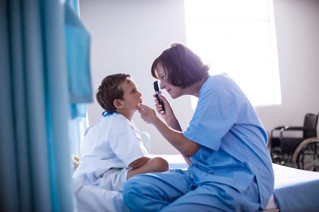 Médica examinando o olho do paciente usando o dispositivo oftálmico