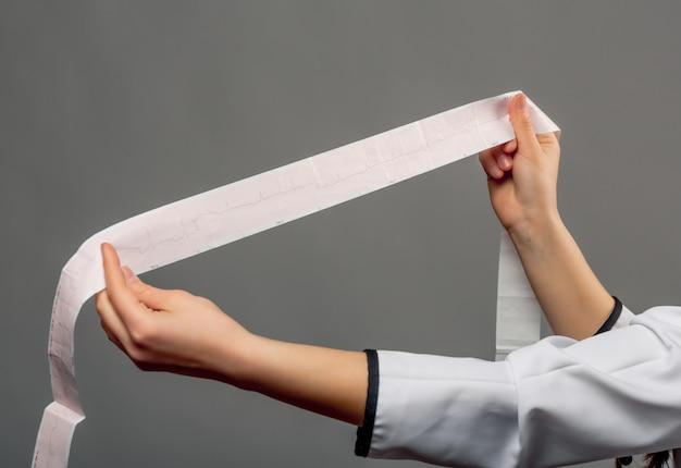 Médica examinando o resultado do ecg do paciente em uma longa lista de papéis isolada