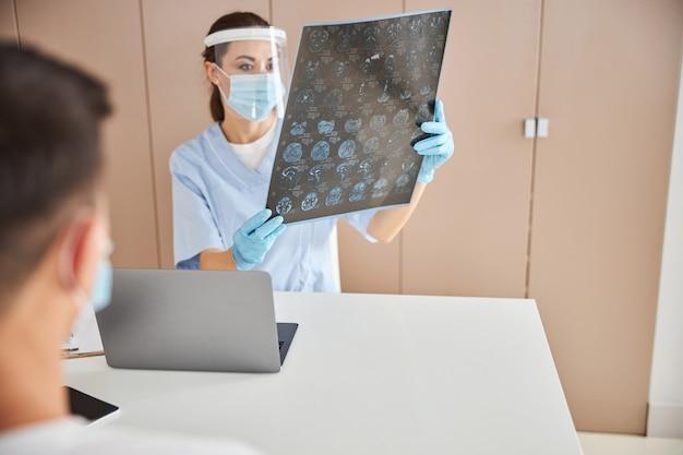 Médica experiente estudando um gráfico de raio x em seu consultório