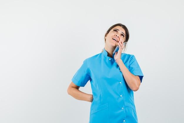 Médica falando no celular com uniforme azul e parecendo pensativa