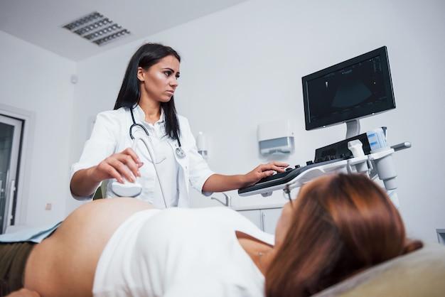 Médica faz ultrassom para uma mulher grávida no hospital.
