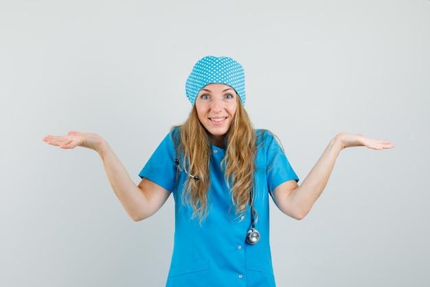 Médica fazendo gesto de escalas em uniforme azul e olhando feliz.