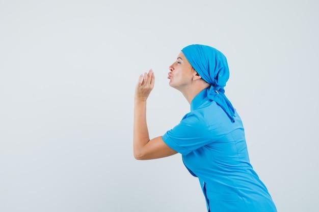 Médica fazendo gesto saboroso com lábios amuados em uniforme azul e parecendo encantada. .