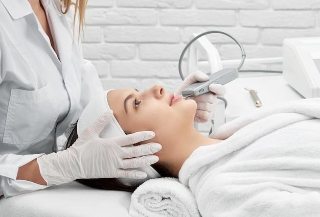 Médica, fazendo o procedimento de limpeza com purificador no spa