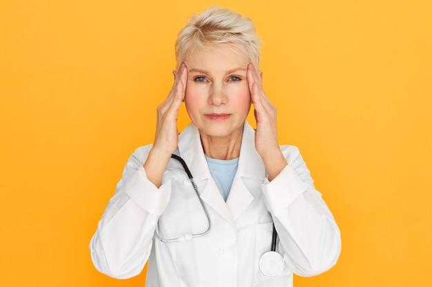 Médica frustrada, madura, em idade de aposentadoria, sofrendo de dor de cabeça ou enxaqueca, tocando as têmporas para aliviar a dor, tendo cansado a expressão facial estressada. estresse e emoções negativas