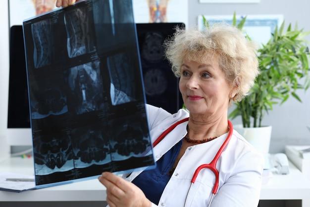 Médica idosa segurando um raio-x em close