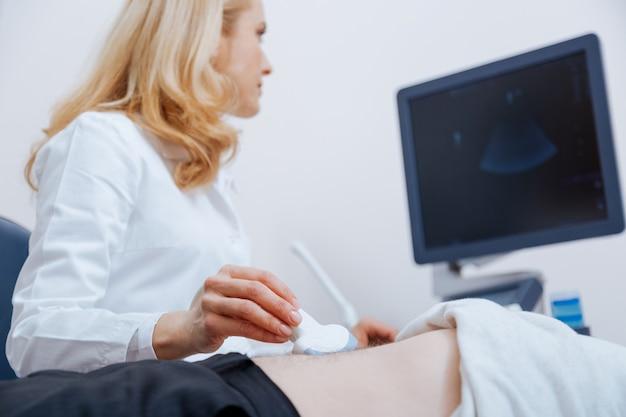 Médica inteligente e qualificada que trabalha na clínica enquanto fornece varredura ultrassônica do estômago e usa transdutor linear de ultrassom e máquina de ultrassom