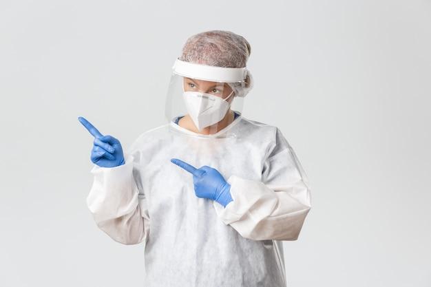 Médica intrigada e atenciosa em equipamentos de proteção individual, protetor facial e luvas, olhando e apontando para o canto superior esquerdo