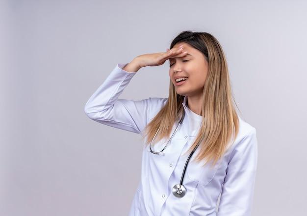 Médica jovem bonita vestindo jaleco branco com estetoscópio em pé com a mão na cabeça por engano, parecendo confusa