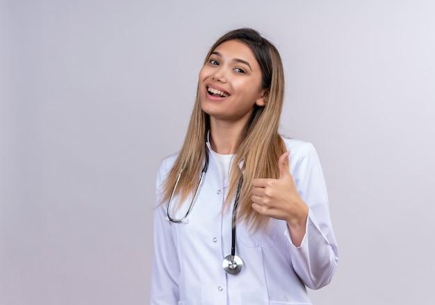 Médica jovem bonita vestindo jaleco branco com estetoscópio, parecendo feliz e animada mostrando os polegares para cima