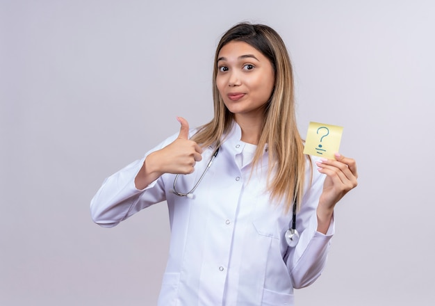 Médica jovem bonita vestindo jaleco branco com estetoscópio segurando um papel lembrete com ponto de interrogação positivo e feliz mostrando os polegares para cima
