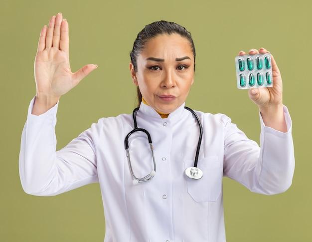 Médica jovem com jaleco branco com estetoscópio em volta do pescoço segurando uma bolha com comprimidos com expressão cética, fazendo gesto de parada com a mão em pé sobre a parede verde