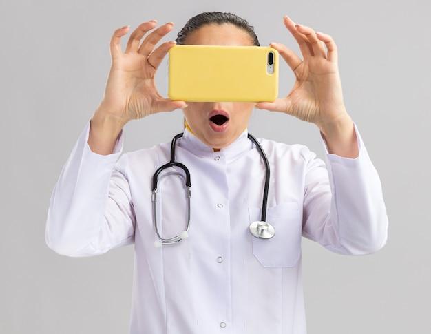 Médica jovem com jaleco branco e estetoscópio pendurado no pescoço segurando o smartphone na frente do rosto, sendo surpreendida