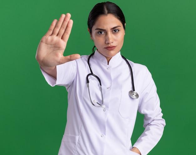 Médica jovem com jaleco e estetoscópio pendurado no pescoço, olhando para a frente com uma cara séria, mostrando um gesto de parada com a mão aberta em pé sobre a parede verde