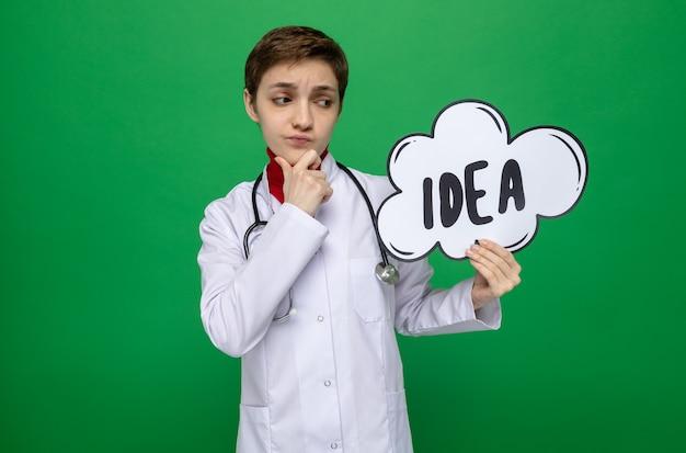 Médica jovem de jaleco branco com estetoscópio segurando um cartaz de bolha do discurso com a ideia da palavra, parecendo confusa com a mão no queixo pensando em pé no verde