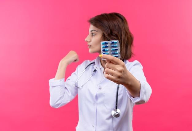 Médica jovem de jaleco branco com estetoscópio segurando uma bolha com comprimidos apontando para algo atrás