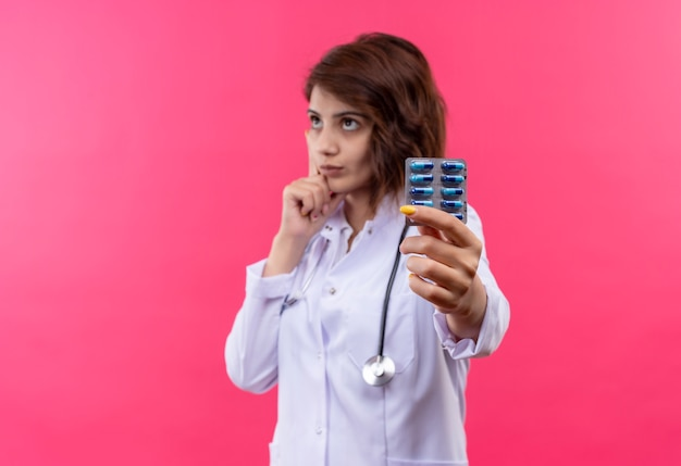 Médica jovem de jaleco branco com estetoscópio segurando uma bolha com comprimidos olhando para o lado com uma expressão pensativa no rosto