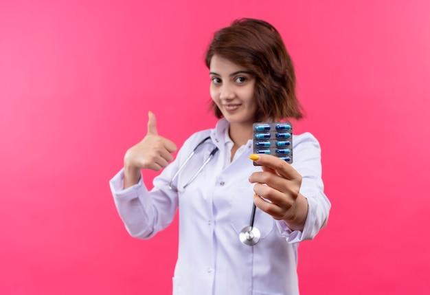 Médica jovem de jaleco branco com estetoscópio segurando uma bolha com comprimidos sorrindo mostrando os polegares para cima