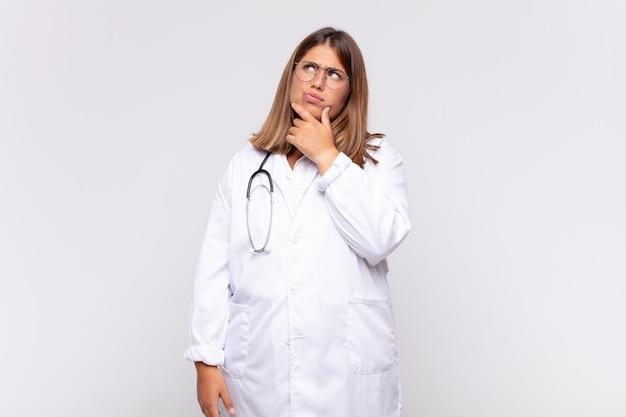 Médica jovem pensando, sentindo-se duvidosa e confusa, com opções diferentes, imaginando qual decisão tomar