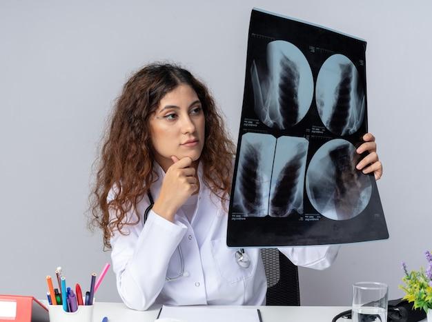 Médica jovem pensativa, vestindo túnica médica e estetoscópio, sentada à mesa com ferramentas médicas, segurando o queixo, segurando e olhando para a foto de raio-x isolada na parede branca