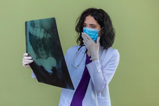 Médica jovem preocupada, vestindo jaleco branco com estetoscópio na máscara protetora médica, parecendo nervosa com a radiografia de pulmões em pé no verde isolado