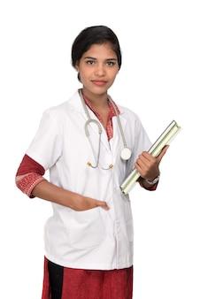 Médica jovem segurando um livro com um estetoscópio
