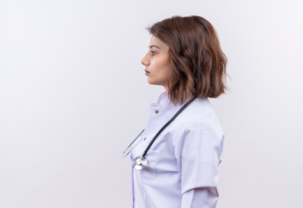 Médica jovem vestindo jaleco branco com estetoscópio em pé de lado com cara séria sobre fundo branco