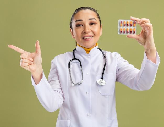 Médica jovem vestindo jaleco branco com estetoscópio no pescoço segurando uma bolha com comprimidos, olhando para a câmera com um sorriso no rosto apontando com o dedo indicador para o lado na parede verde