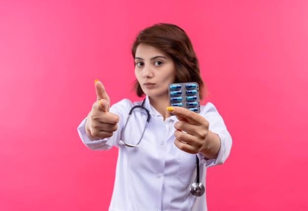 Médica jovem vestindo jaleco branco com estetoscópio segurando uma bolha com comprimidos apontando com o dedo para a câmera com uma cara séria