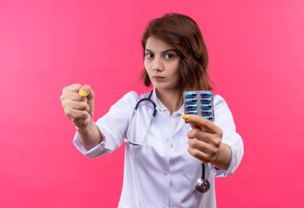Médica jovem vestindo jaleco branco com estetoscópio segurando uma bolha com comprimidos, mostrando o punho para a câmera com uma cara séria
