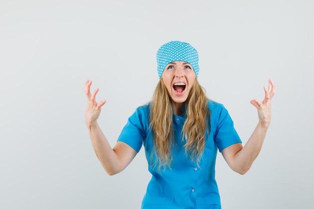 Médica levantando as mãos de maneira agressiva em um uniforme azul e parecendo nervosa