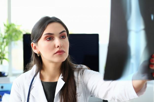Médica linda segurar no braço e olhar para o raio x