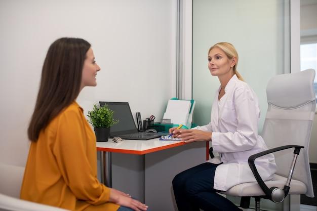 Médica loira com túnica branca falando com sua jovem paciente