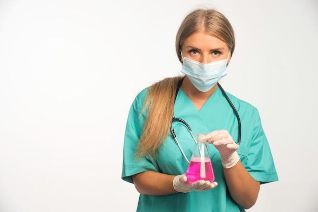 Médica loira de uniforme azul com estetoscópio no pescoço, máscara facial e segurando um frasco químico