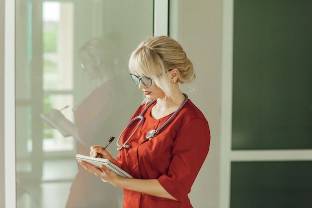 Médica loira de uniforme vermelho com um estetoscópio de pé no hospital, escreve algo em um caderno.