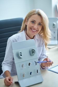 Médica loira e atraente, loira, sorridente, usando um jaleco, demonstrando um conjunto de vários surdos-auxiliares