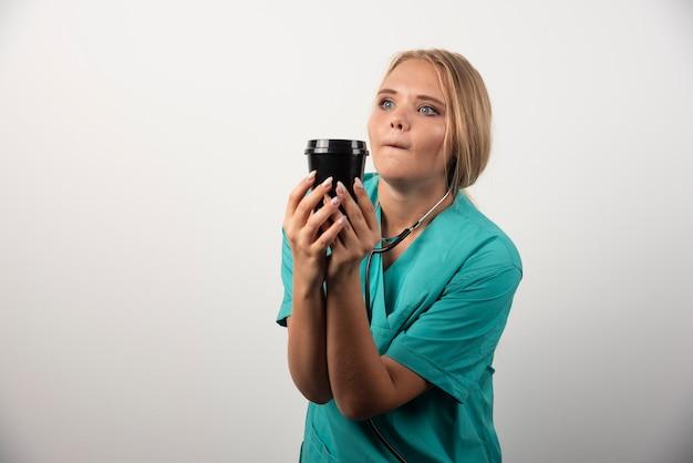 Médica loira posando com uma xícara de café.