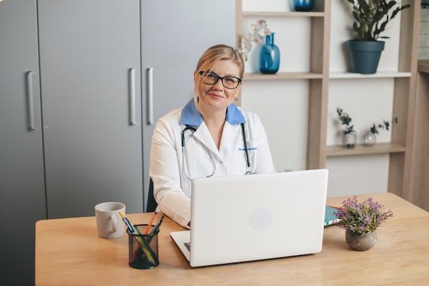 Médica loira sênior feliz sorrindo para a câmera enquanto usa um laptop no escritório