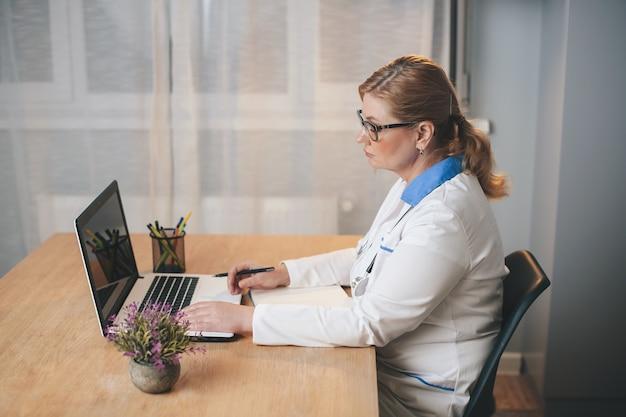 Médica loira sênior no escritório usando um laptop durante o dia de trabalho